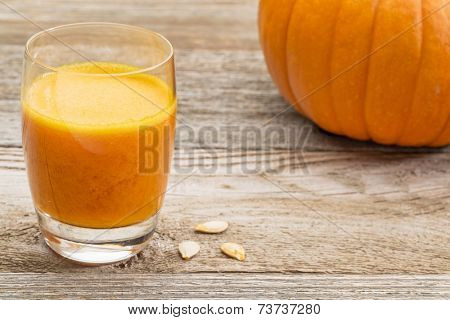 a glass of fresh pumpkin juice on a rustic wooden table with pumpkin and seeds