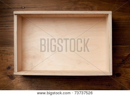 Empty wooden box on brown background.