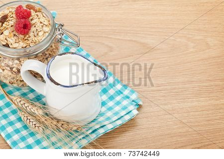 Healty breakfast with muesli, berries and milk. On wooden table with copy space