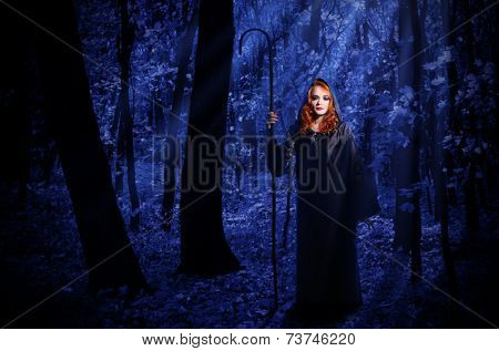 Young witch at night in the moonlight forest