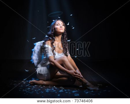Young woman as an angel on dark background