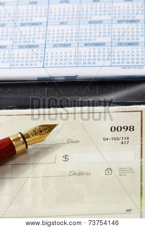 An open checkbook and a ballpen, closeup