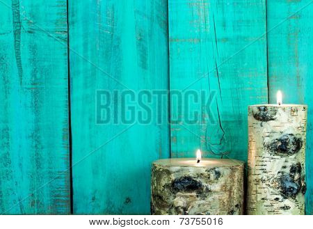 Textured log candles burning by antique teal blue wooden old wall
