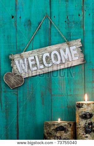Wood welcome sign with heart and burning log candles hanging on rustic antique green door
