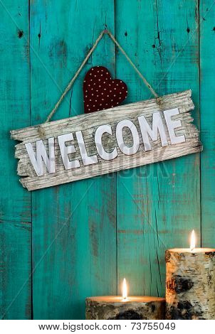 Wood welcome sign with red heart by candlelight hanging on antique teal blue background