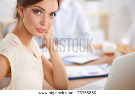 Attractive businesswoman sitting  in the office, isolated