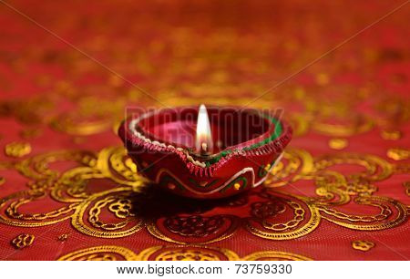 A decorative Diwali lamp against glittering background