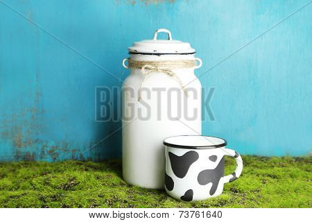 Retro can for milk and mug of milk on wooden background