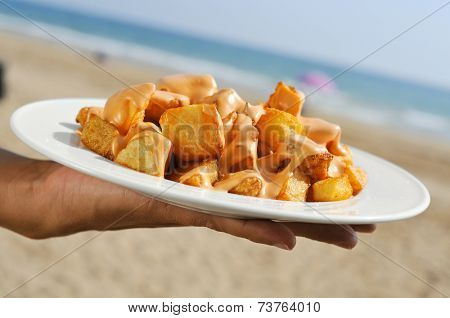 closeup of a plate with typical spanish patatas bravas, fried potatoes with a hot sauce, on the beach