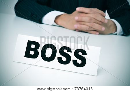 a man wearing a suit sitting in a desk with a nameplate in front of him with the word boss written in it