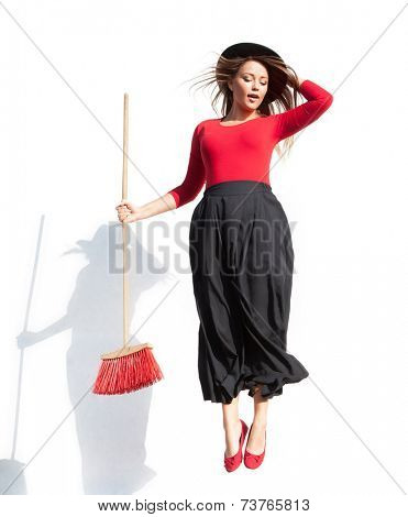Young attractive woman wearing witch fancy dress flying with a broom, halloween concept