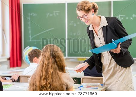 Teacher or docent or educator giving while lesson in front of a blackboard or board a sheet of paper and educate or teaching students or pupils or mates in a school or class