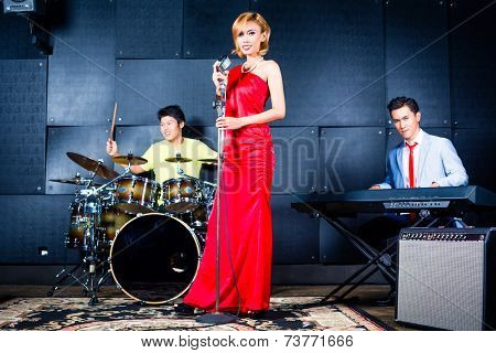 Asian professional singer drummer and keyboarder recording new song or album in studio