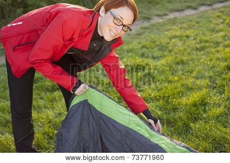 Young Woman unwrapping Slepping Bag