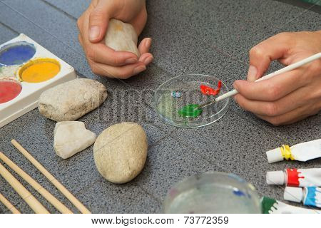 Stone Painting. Dunking Brush Into The Paint