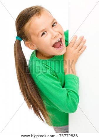 Little girl is looking from out blank board and showing thumb up sign, isolated over white