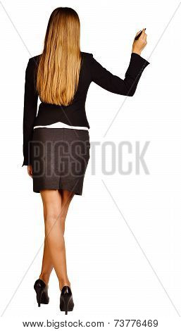Business woman holding a pen and writing in the air with her legs crossed.