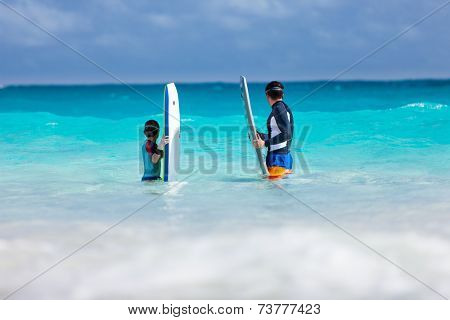 Father and son in ocean with boogie boards waiting for a wave