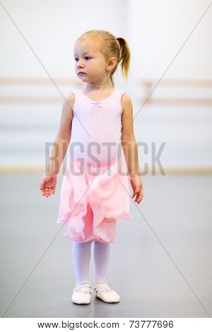 Adorable little ballerina wearing pink leotard in a dancing school