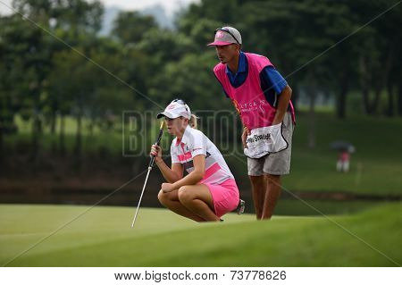 KUALA LUMPUR, MALAYSIA - OCTOBER 11, 2014: Jodie Ewart Shadoff of England reads the lines on the green of the ninth hole of the KLGC Club during the 2014 Sime Darby LPGA Malaysia golf tournament.