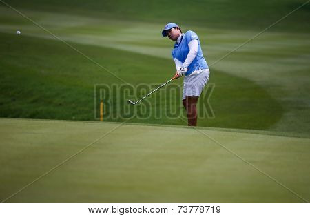 KUALA LUMPUR, MALAYSIA - OCTOBER 10, 2014: Ariya Jutanugarn of Thailand chips the ball to the 18th hole of the KL Golf & Country Club at the 2014 Sime Darby LPGA Malaysia golf tournament.