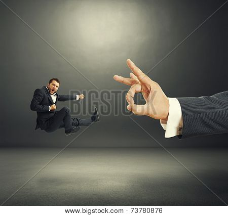 concept photo of conflict between subordinate and boss. emotional young businessman kicking and screaming, big hand flicking. photo in the dark room