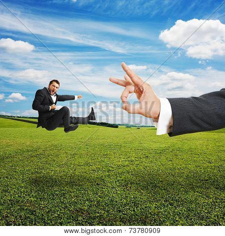 concept photo of conflict between subordinate and boss. angry young businessman kicking and flying at big flick of his boss. photo at outdoor