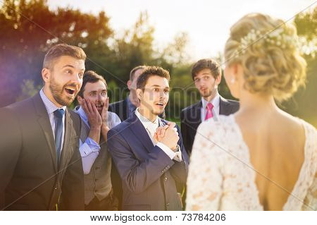 Groomsmen looking at bride
