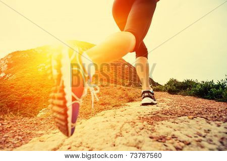 young woman legs running on seaside mountain trail