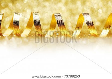 Curly golden serpentine on shiny glitter background, holiday concept
