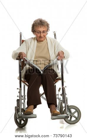 80 Year Old Elderly Senior Woman Sit in Wheelchaire Reading Magazine Isolated on White Background