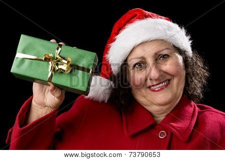 Elderly Woman Holding Up A Green Wrapped Xmas Gift.