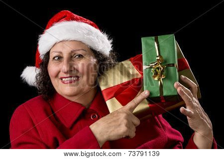 Senior Lady With Santa Cap Points At Wrapped Gifts.