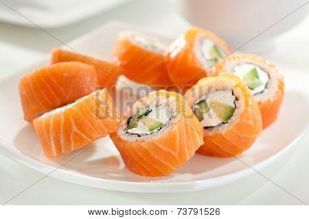 Philadelphia Maki Sushi made of Cream Cheese, Cucumber and Avocado inside. Salmon outside