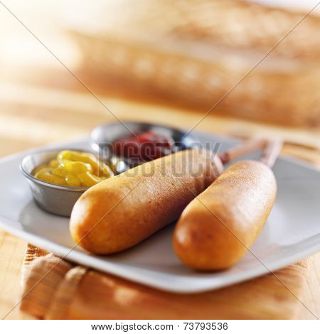 two corn dogs on plate with ketchup and mustard