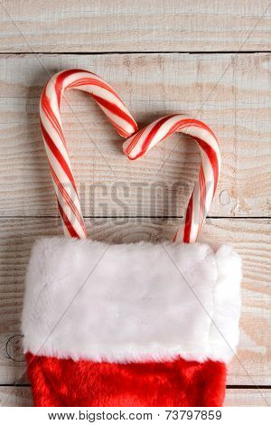 High angle image of a Christmas Stocking with two candy canes forming a heart shape on a whitewashed wood table. Vertical Format.