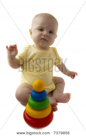 The Baby Of 6-7 Months Sits With A Pyramid And Is Angry