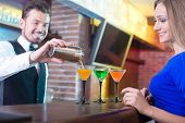 picture of bartender  - Handsome bartender serving cocktail to attractive woman in a classy bar - JPG