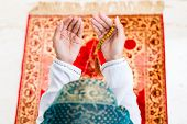 stock photo of prayer beads  - Asian Muslim woman praying on carpet with beads chain wearing traditional dress - JPG