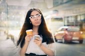 image of saddening  - Expressive woman holding phone and cup of coffee out in the city - JPG