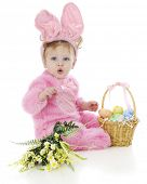 stock photo of baby easter  - An adorable baby girl attempting to whistle in her fluffy pink Easter bunny outfit - JPG