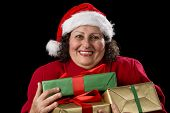 foto of gold tooth  - Happy female senior is pressing three wrapped Christmas presents close to her chest - JPG