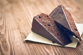 stock photo of torte  - portion of sacher cake on wooden table - JPG