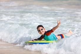 foto of boogie board  - Little boy on vacation having fun swimming on boogie board - JPG
