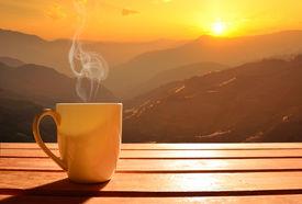 stock photo of morning sunrise  - Morning cup of coffee with mountain background at sunrise - JPG