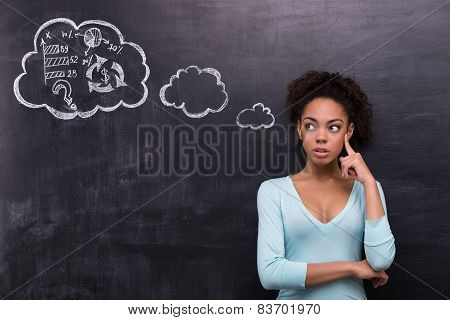 Thoughtful afro-american woman trying to solve a problem on chalkboard