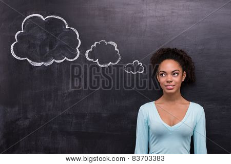Smiling afro-american woman with cloud formed dialog on chalkboard