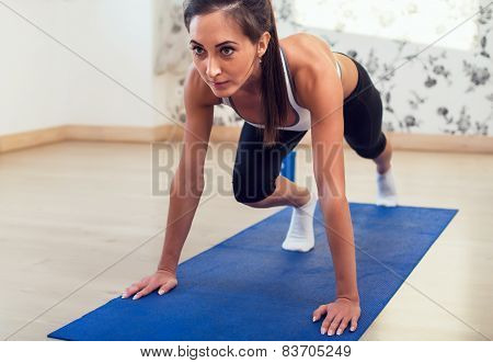 Young athletic sporty slim woman doing exercises on the blue mat looking straight forward.
