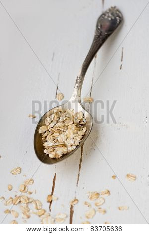 One Tablespoon Of Oatmeal Is A White Wooden Background. Healthy Food.