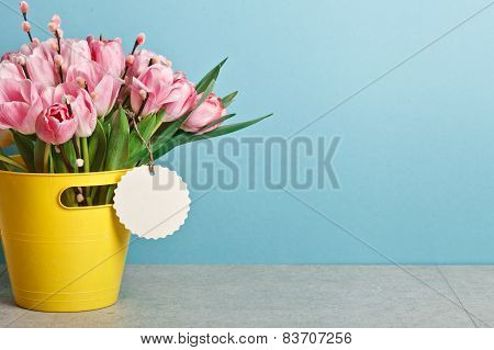 Bouquet Of Pink Fresh Tulips With Pussy-willow In Yellow Bucket On Table On Blue Background